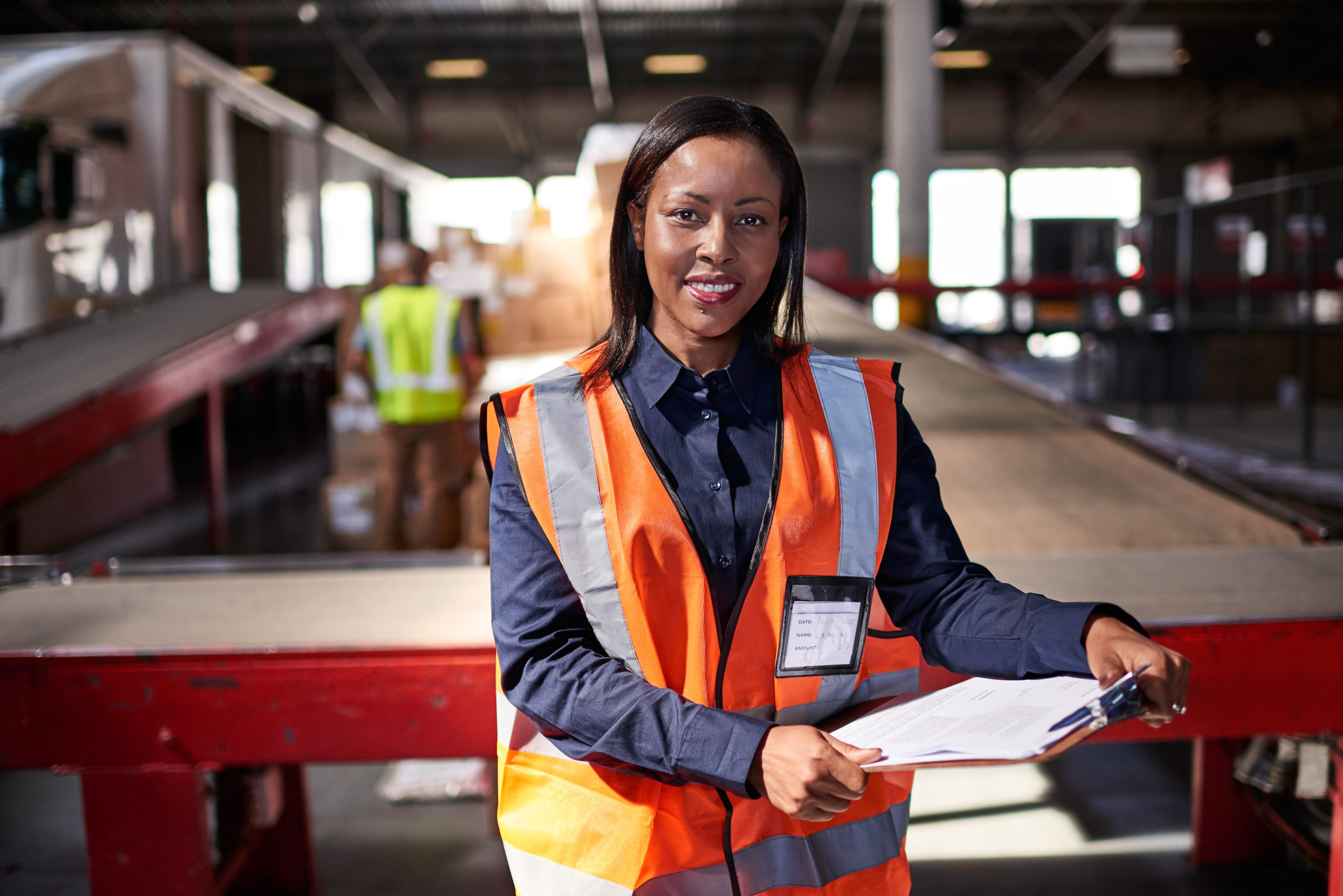 Portrait of a warehouse manager holding a clipboard with workers in the background